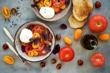 Caprese salad of colorful tomatoes. Tomatoes, mozzarella, basil and spices. Mediterranean cuisine, Italy