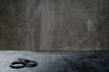 front view of metal handcuffs on table in the interrogation room
