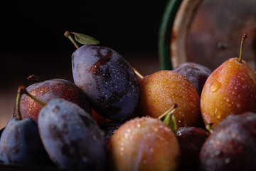 Purple, blue and yellow plums on a wooden table