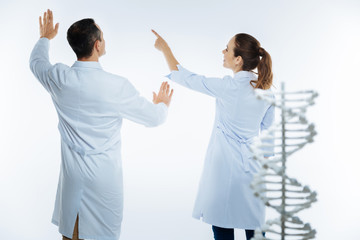 Joyful medical coworkers using invisible screen while studying genetics
