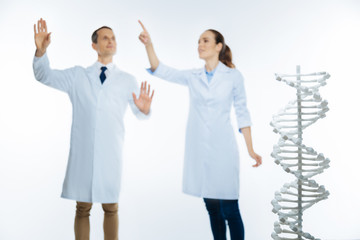 Selective focus on dna model with coworker behind