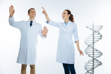 Radiant medical professionals using invisible screen while working with dna