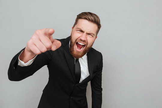 Angry businessman in suit shouting and pointing finger at camera