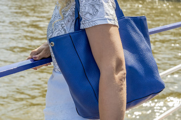 Shoulder bag on woman shoulder. Woman standing near the water