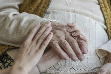 wrinkled hand holding a younger hands