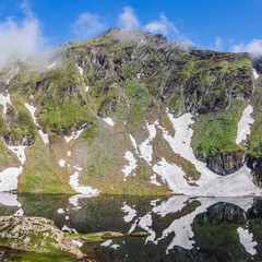 Tuinposter Reflectie Nature landscape of amazing glacier lake Balea and Fagaras mountains with white spots of snow reflected in the water at Carpathians, Romania