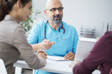 Male doctor talking to young couple