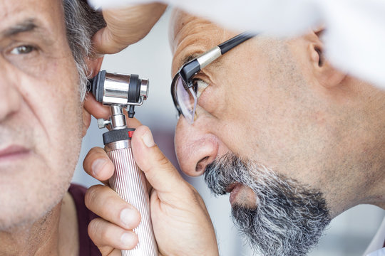 Doctor holding otoscope and examining ear of senior man