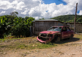 Broken and rusty car left abandoned in lush environment in the outskirts of Boston Bay in Portland parish, Jamaica on 30 December 2013.