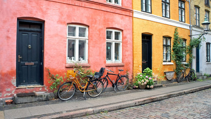 Papiers peints Velo Colorful street, doors, windows, red and yellow walls and bikes with basket in old town, Copenhagen, Denmark