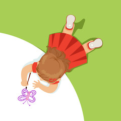 Little girl lying on her stomach and painting a purple butterfly, top view of child on the floor