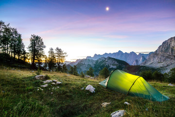 Wall Mural - A tent glows under a moon night sky at twilight hour. Alps, Triglav National Park, Slovenia.