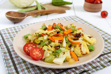 Vegetable stew - a mixture of baked cabbage, green beans, onions, carrots, cherry tomatoes, sweet pepper on a plate on a white wooden background. Vegan cuisine. Proper nutrition.