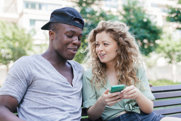Engaged couple talking using smart-phone on bench in a park during summer