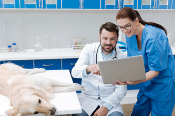 Positive delighted lab assistant holding laptop