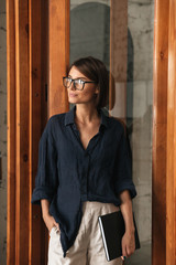 Vertical image of business woman in eyeglases with folder