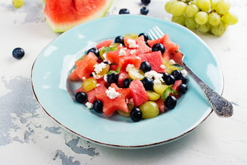 Fresh watermelon salad with feta cheese and berries on white stone table. Space for text