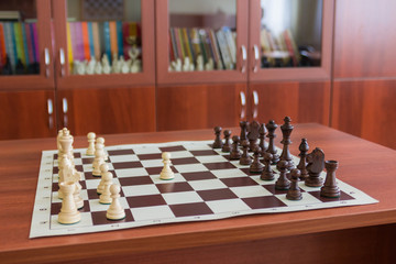 Wooden chess pieces on a chess Board.