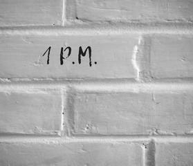 PHOTO OF 1 P.M. WRITTEN ON WHITE PLAIN BRICK WALL