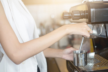 Young Barista girl prepares coffee in the coffee shop or cafe restaurant