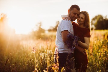 Cheerful couple hugs each other tender standing on the green field