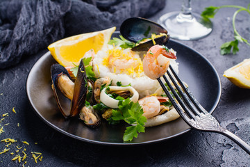 Seafood saute with rice on black stone table