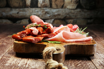 Marble cutting board with prosciutto, bacon, salami and sausages on wooden background. Meat platter