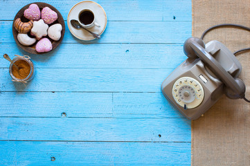 Old vintage telephone, with biscotti, caffè, donuts on a wooden background, free space for text