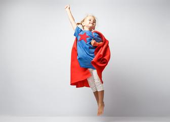 Very excited little girl dressed like superhero jumping alongside the white wall.