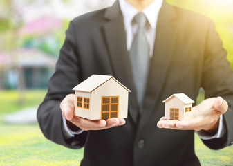 businessman hold big and small houses on hand Papier Peint