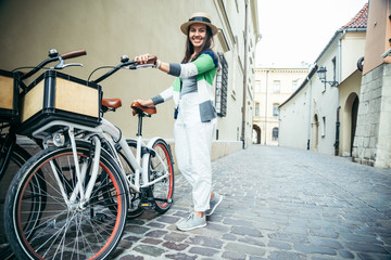 woman stading near bicycle that parked in old narrow european street