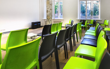 Empty lecture hall - small class room with green and black plastic chairs and big bright windows. Comfort space for learning.