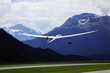 A glider is flying in the alps