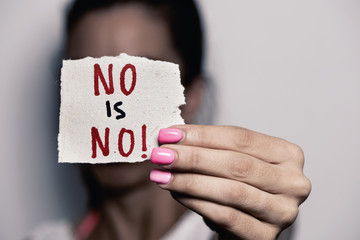 woman showing a note with the text no is no