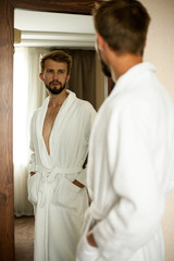 Young man in bathrobe stands in front of mirror and looks at his reflection..