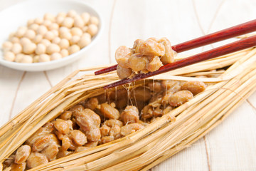 Natto and soy beans on white background