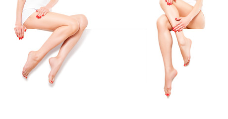 Two beautiful slim womans with red manicure, sitting at banner, isolated on white background
