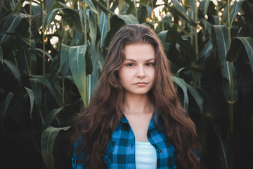 Young girl in blue checkered shirt on a background of corn field