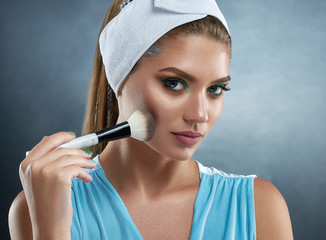 Front view of beautiful woman with perfect skin, wearing in bandage on head, drawing blush for herself. Girl holding cosmetic ankle, making professional makeup, looking at camera. Beauty concept.