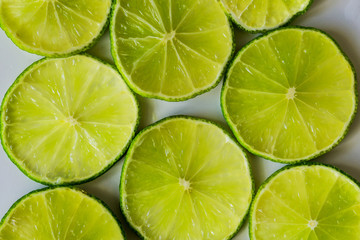Close-up of lime slices on a white background, suitable for texture and background. Health concept.
