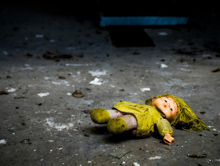 Abandoned doll on dirty floor