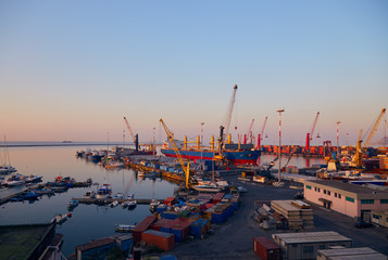 Port terminal with cranes, ships and containers near Salerno at dawn
