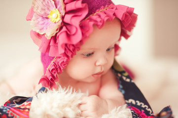 Cute baby girl wearing stylish knitted hat lying in bed closeup. Looking away. Childhood.