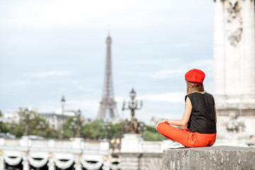 Young woman in red hat enjoying great view on Eiffel tower sitting on the bridge in Paris