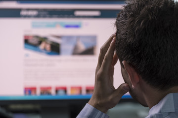 Man overwhelmed with what he sees on his computer screen