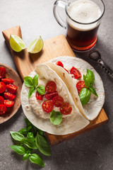 Home tortilla with hummus of white beans and beer on a gray stone table. Italian, Mediterranean style. With tomatoes and basil . dark beer