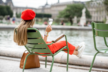 Young stylish woman in red cap and pants sitting with glass of wine on the famous green chairs in Tuileries garden in Paris Wall mural