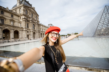 Young woman tourist in red cap making selfie photo in front of the famous Louvre pyramids in Paris