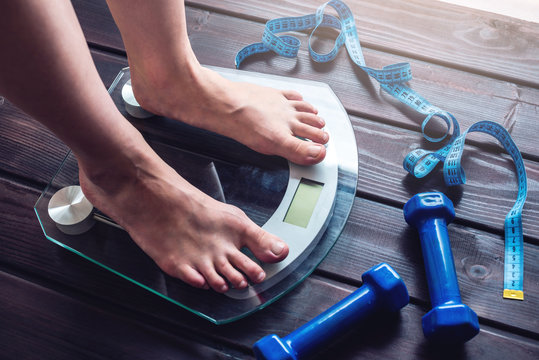 Female feet standing on electronic scales, dumbbells and measuring tape. Concept of slimming and weight loss