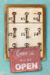 Small vintage cabinet with rusted hotel keys and open sign